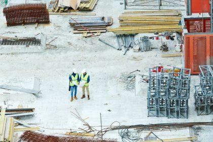 Building inspectors reading blueprint on construction site